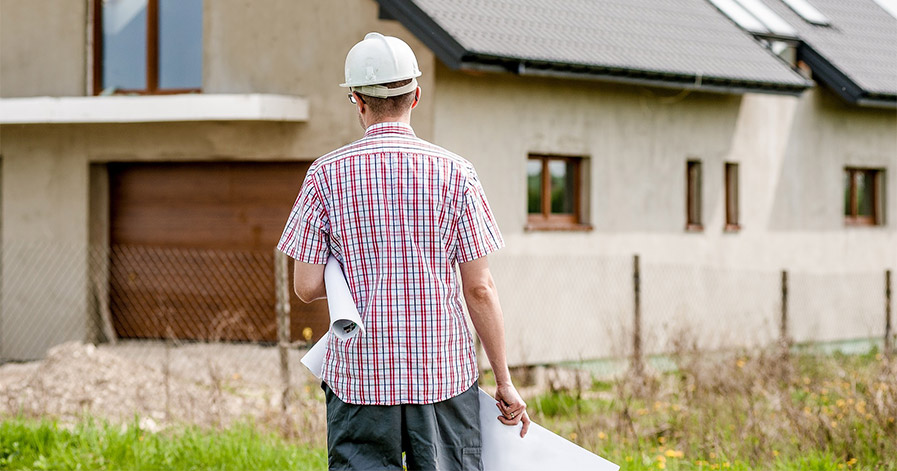 Man with hard hat and blue print standing outside a house