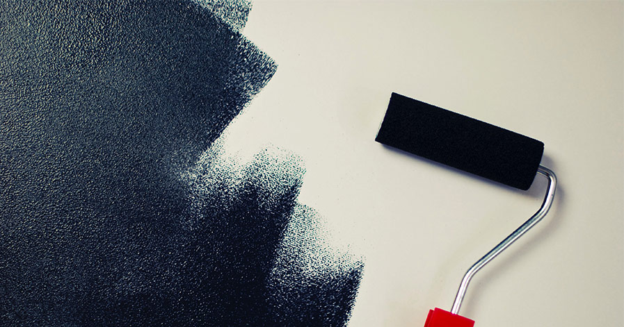 Paint roller painting blue on a white wall