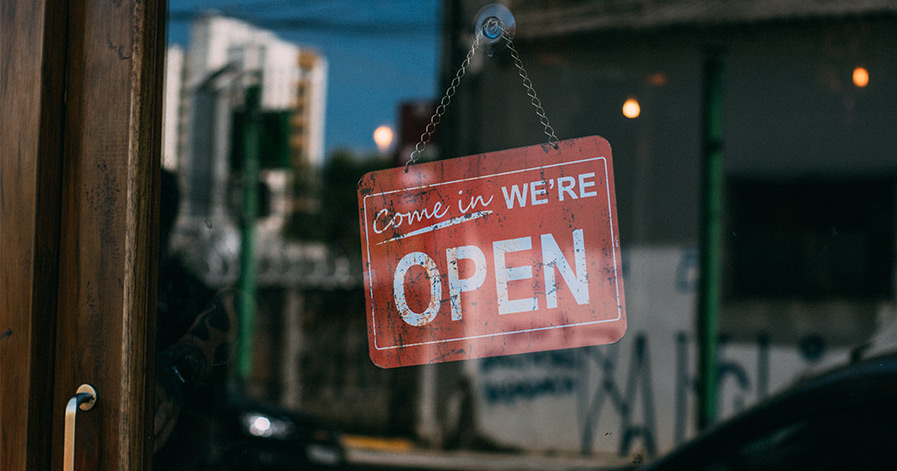 """Come in we're open"" sign on glass door"