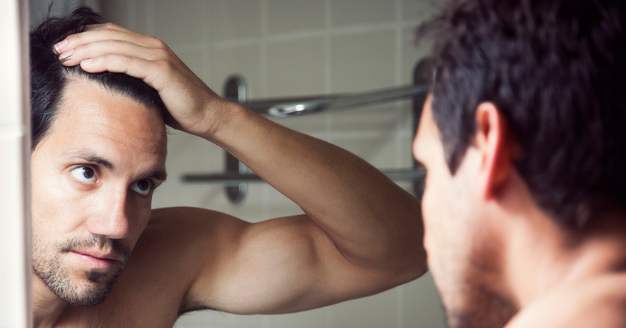 Man looking in mirror at his hair