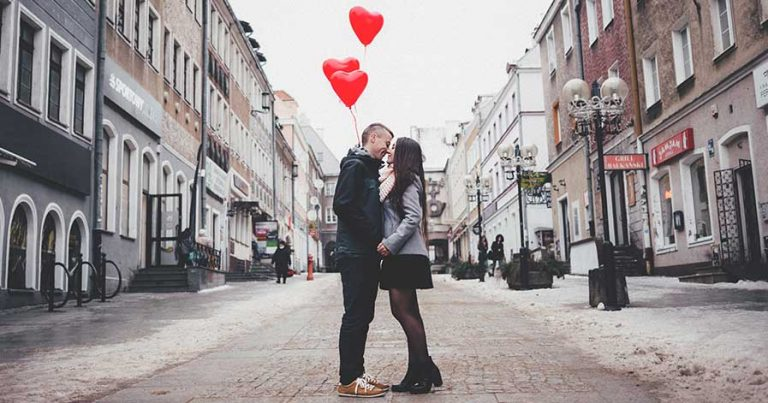 A couple kissing in the street, holding heart-shaped balloons