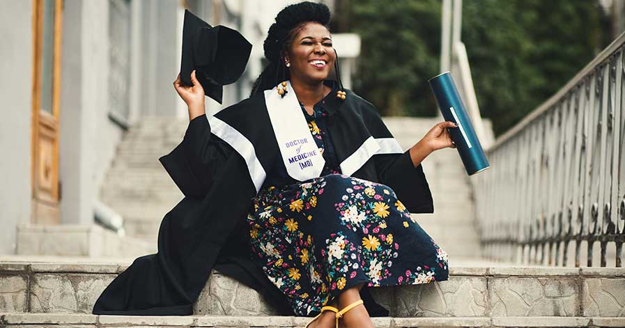A woman sitting on steps, holding her college degree after a graduation ceremony