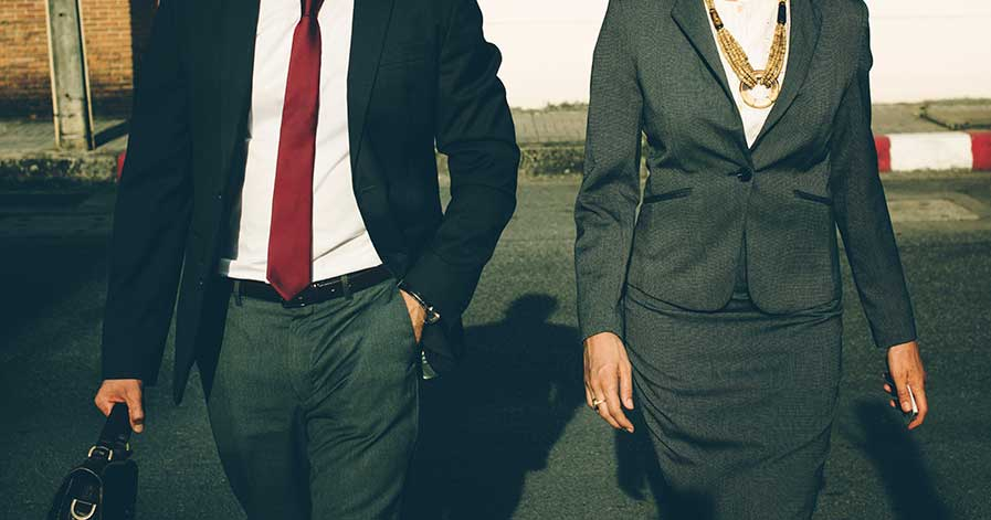 A man and woman wearing business casual outfits.