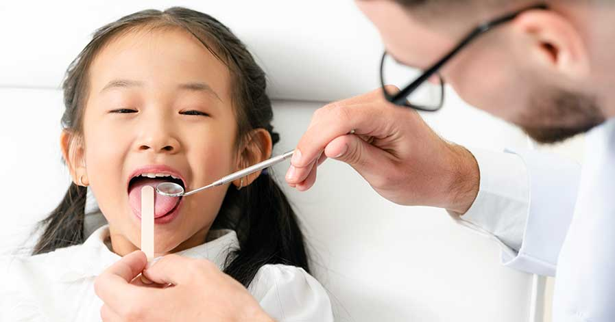 A young girl gets a checkup at the dentist