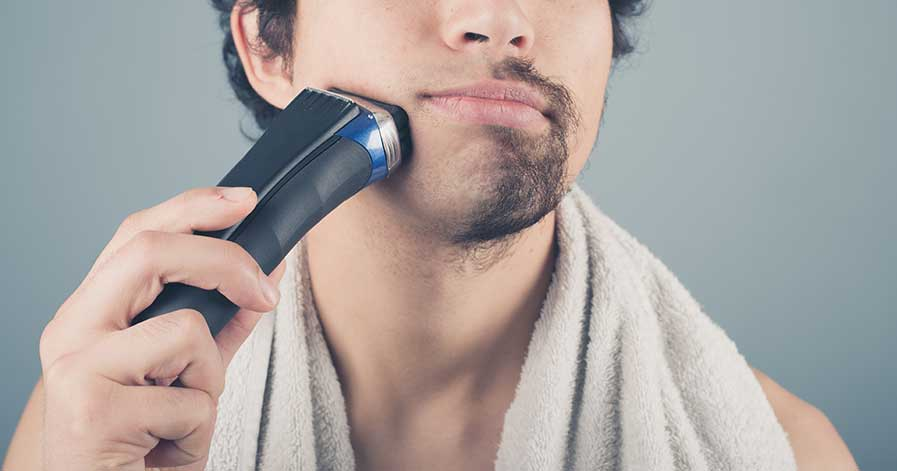 A man using an electric razor