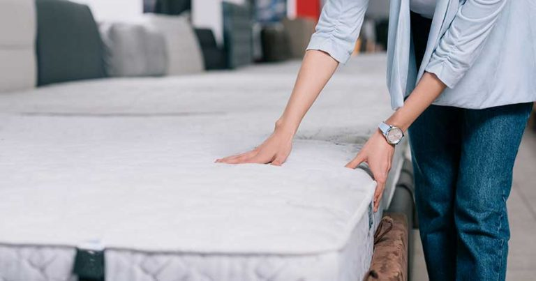 A woman feeling a mattress in a mattress store