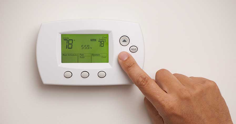 A hand adjusting the temperature on a thermostat