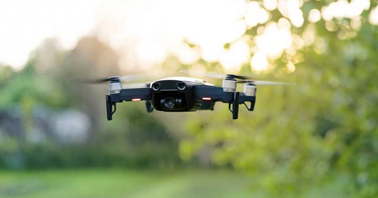 A drone flying in front of some trees
