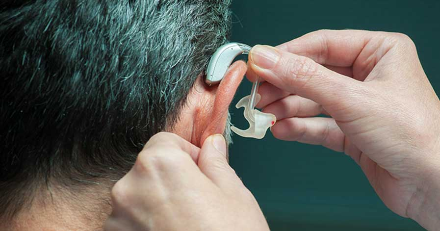 A man putting a hearing aid into his ear