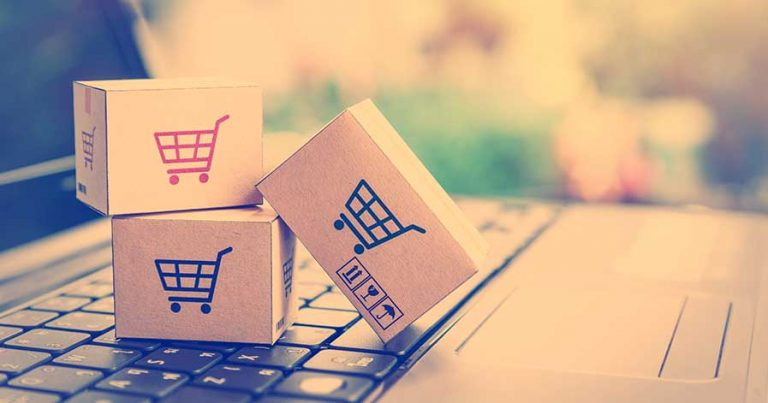Small boxes with shopping carts on them, stacked on a laptop keyboard