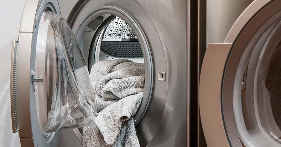 A washing machine filled with white towels