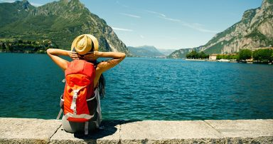 Backpacker sitting beside lake