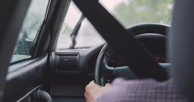 Hands on steering wheel of car