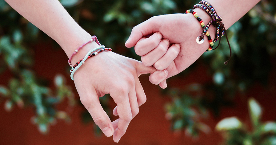 Two hands with friendship bracelets on