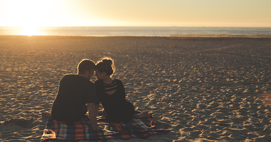 Couple sitting on beach and sunset