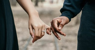 Man and woman holding pinkies, woman wearing engagement ring