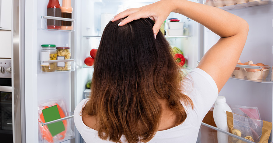 Woman confused standing in front of open fridge