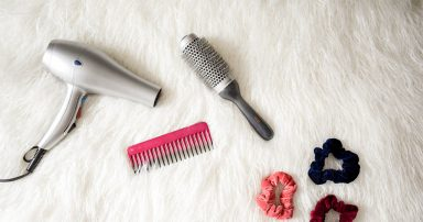 Blow dryer, scrunchies and brushes on carpet