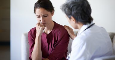 Woman looking upset with doctor comforting her