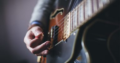 Person strumming on guitar