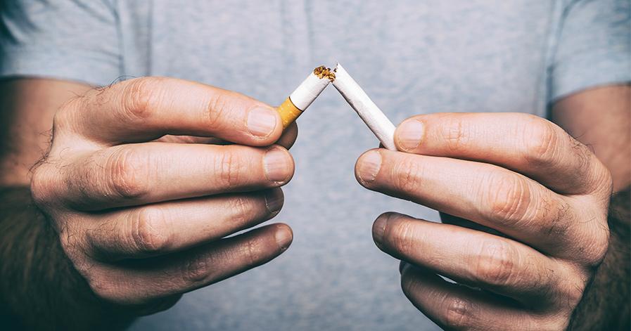 Man breaking cigarette in two
