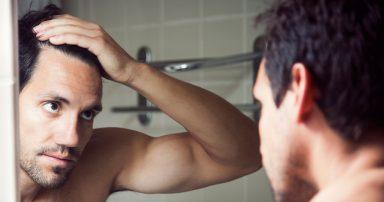 Man looking in mirror at his hair