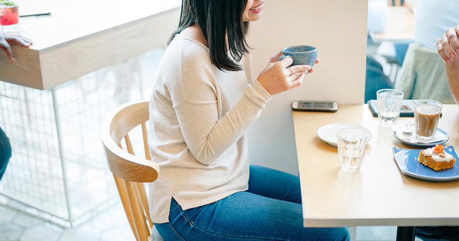 Woman sitting in cafe with phone