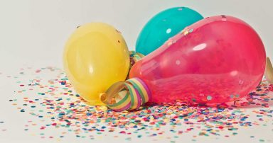 Balloons and confetti on a table.