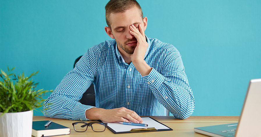 Man looking stressed sitting at a desk