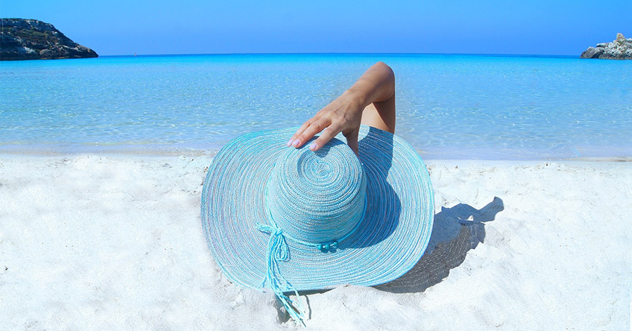 Woman with blue sunhat lying on the beach in the sunshine