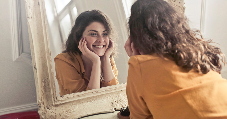 Woman staring in mirror and smiling