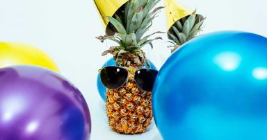A pineapple wearing a party hat, surrounded by balloons.