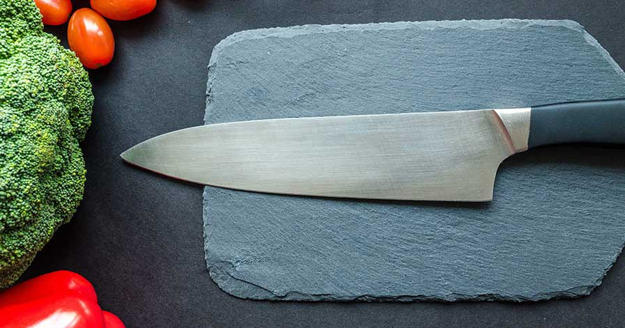A knife on a cutting board, sitting beside vegetables