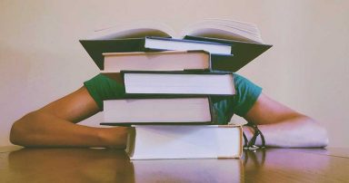 A student studying behind a pile of books