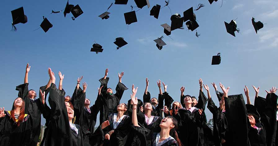 A group of college graduates throwing their caps in the air
