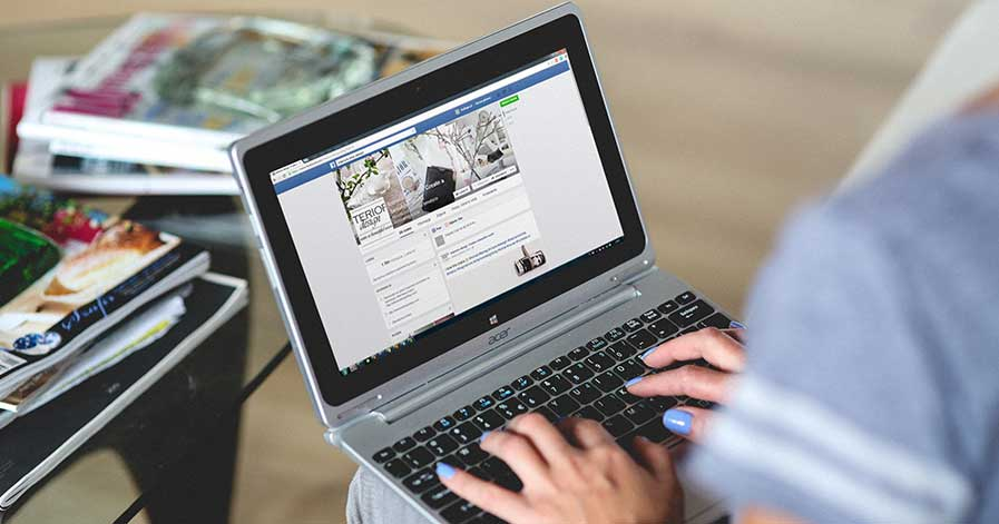 A woman working on her computer, setting up a Facebook business page
