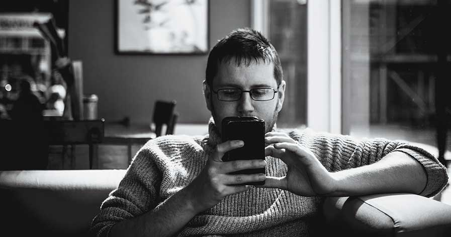 A man scrolling through his phone