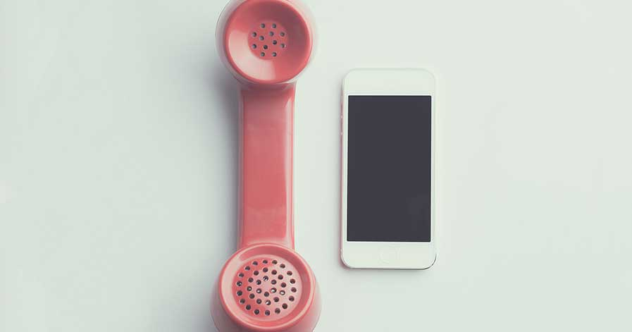 An apple phone on a table beside a landline phone
