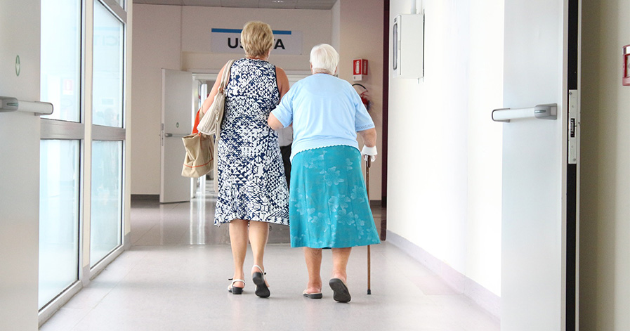Woman and older woman walking down hall at hospital