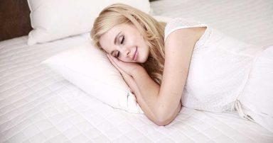 A woman laying down on a mattress