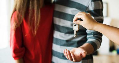 A couple being handed the key to a new home