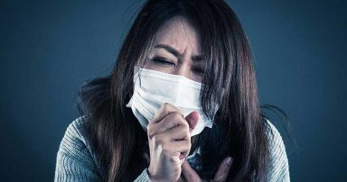 A woman sneezing into a face mask