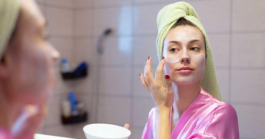 A woman applying night cream.