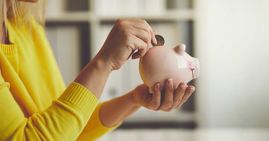 A woman putting money in a piggy bank