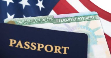 An American passport and green card on top of an American flag