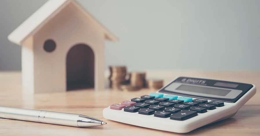A calculator sitting on a table with a pen, and a wooden house in the background