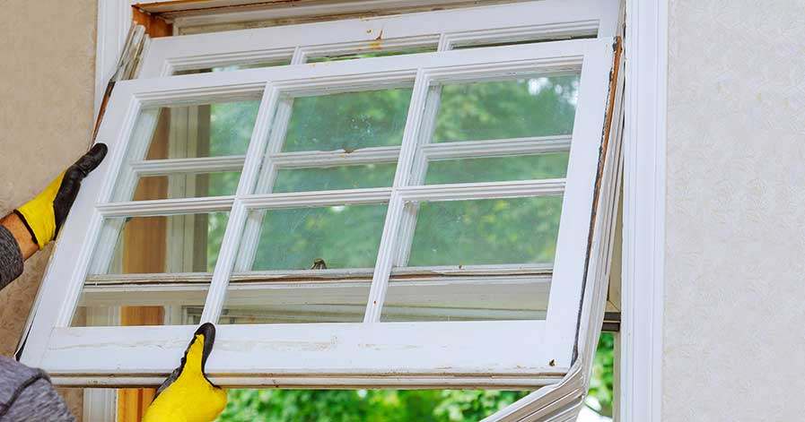A man replacing a window in his house
