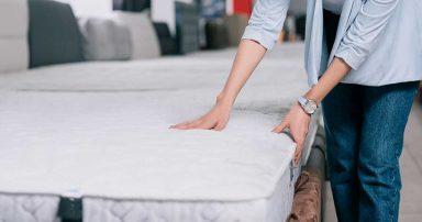 A woman feeling a mattress in a mattress store