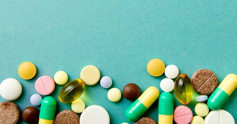 Various vitamins and pills on a blue background