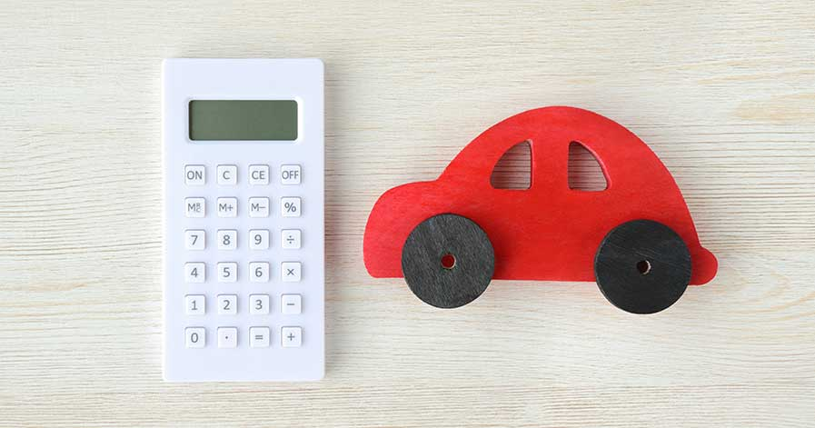 A red toy car beside a calculator